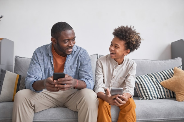 Fröhlicher teenager, der spaß mit seinem vater hat, der zusammen videospiele auf smartphones spielt, während er zu hause bleibt, mittelhohe aufnahme