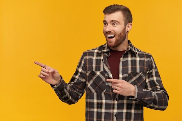 Fröhlicher, überraschter junger bärtiger mann in kariertem hemd, der mit zwei fingern über der gelben wand auf den copyspace schaut und zur seite zeigt