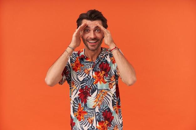 Fröhlicher überraschter junger mann mit stoppeln im hawaiianischen hemd, das einen boo mit den händen späht und gesicht zeigt