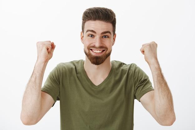 Fröhlicher und energiegeladener aktiver süßer männlicher fan mit bart im t-shirt, der geballte fäuste in sieg und triumph erhebt und den gewinn des ersten preises feiert, der vor aufregung lächelt und über weiße wand erfreut ist