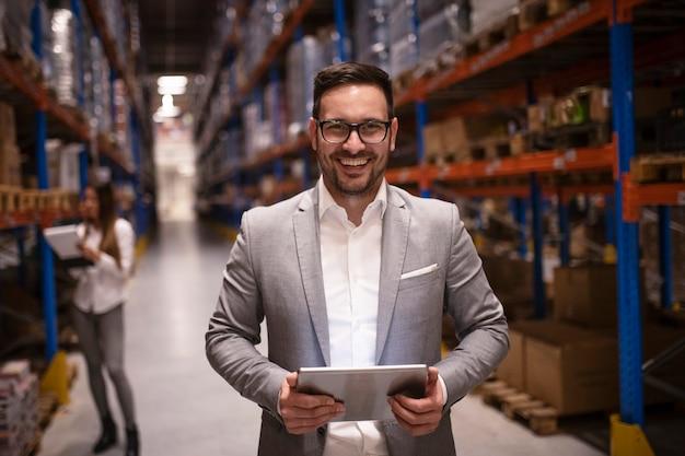 Fröhlicher und erfolgreicher manager-geschäftsmann mittleren alters, der tablet-computer im großen lager hält, das verteilung verteilt