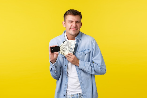 Fröhlicher und erfreuter, glücklicher blonder kerl, der aufgeregt aussieht, zufrieden lächelt, als zusätzliche barzahlung erhält, kreditkarte mit geld hält, gelber hintergrund optimistisch steht.