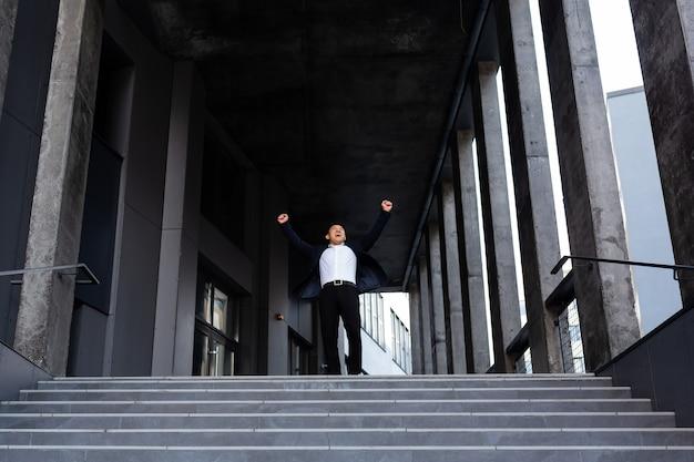 Fröhlicher und fröhlicher asiatischer geschäftsmann, der die hände hochhält und sich über sieg und erfolg in der nähe der vorderansicht des bürozentrums freut