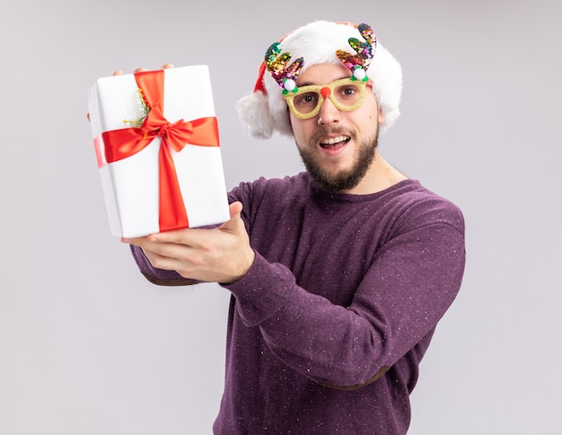 Fröhlicher und fröhlicher junger mann in lila pullover und weihnachtsmütze mit lustiger brille, die ein geschenk zeigt, das in die kamera schaut und breit auf weißem hintergrund lächelt