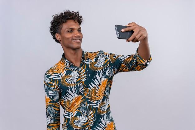 Fröhlicher und lächelnder gutaussehender dunkelhäutiger mann mit lockigem haar im blatt bedruckten hemd, das selfie unter verwendung der telefonkamera macht