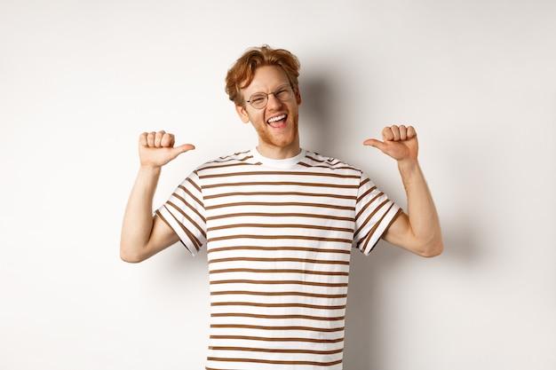 Fröhlicher und lustiger rothaariger mit bart, der eine brille trägt, lacht und auf sich selbst zeigt, auf weißem hintergrund stehend.
