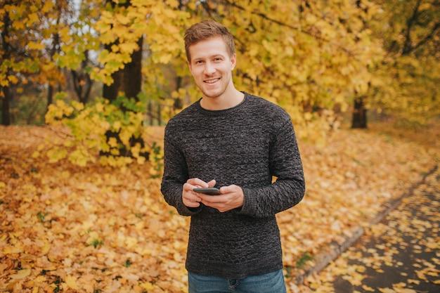 Fröhlicher und positiver junger mann steht und schaut vor der kamera. er schaut vor die kamera und lächelt. junger mann hat telefon in händen.