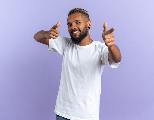 Fröhlicher und zufriedener afroamerikanischer junger mann im weißen t-shirt, der mit zeigefingern auf die kamera zeigt, fröhlich lächelnd auf blauem hintergrund stehend