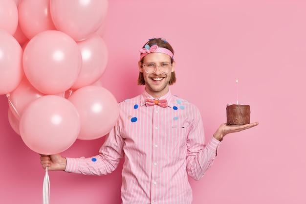 Fröhlicher unrasierter kerl mit trendiger frisur bereitet sich auf geburtstagsfeier vor hält schokoladenkuchen und heliumballons hat spaß auf der party erhält glückwünsche von herumfliegenden freunden konfetti