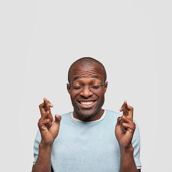 Fröhlicher unternehmer betet für erfolg oder glück, drückt die daumen und schließt die augen, hat ein strahlendes lächeln
