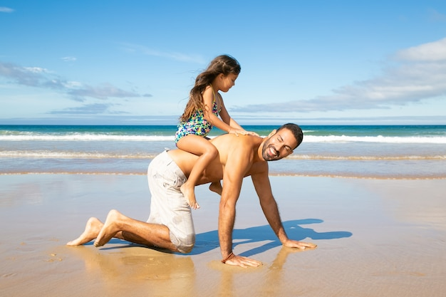 Fröhlicher vater, der am strand auf händen und knien geht und ein kleines mädchen auf dem rücken trägt