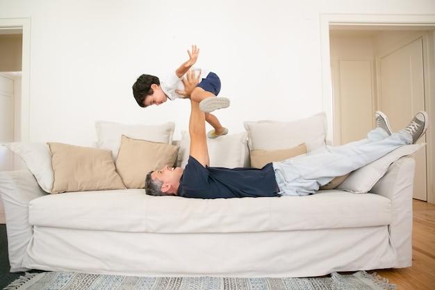 Fröhlicher vater, der auf sofa liegt und sohn hält.