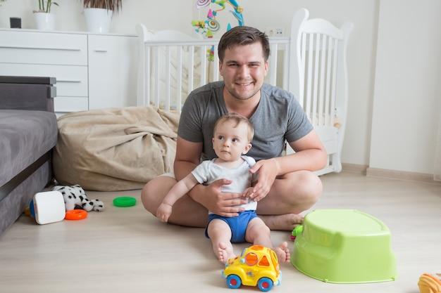 Fröhlicher vater, der spaß mit seinem baby hat und auf dem boden spielt