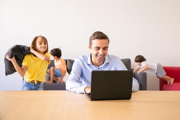 Fröhlicher vater, der über laptop und kinder plaudert, die mit kissen in seiner nähe spielen. kaukasischer vater, der während der schulferien zu hause arbeitet. familien- und digitaltechnikkonzept