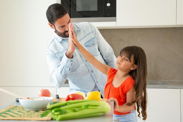 Fröhlicher vater und tochter geben high five beim gemeinsamen kochen in der küche. mädchen und ihr vater schneiden gemüse an der küchentheke. familienkochkonzept