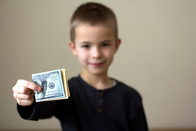 Fröhlicher verschwommener junge, der amerikanisches dollargeld zeigt.