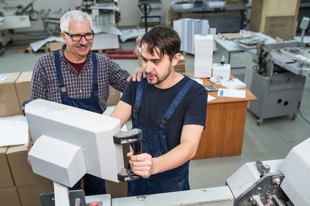 Fröhlicher vorarbeiter, der jungen arbeiter unterstützt, der die einstellungen der druckmaschine im fabrikladen überprüft