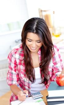 Fröhlicher weiblicher asiatischer student, der mathe in der küche tut