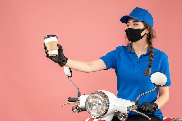 Fröhlicher weiblicher kurier mit schwarzer medizinischer maske und handschuhen, der bestellungen auf pfirsichhintergrund liefert