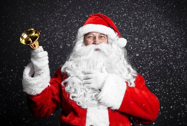 Fröhlicher weihnachtsmann, der handglocke hält