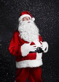 Fröhlicher weihnachtsmann, der seinen bauch berührt