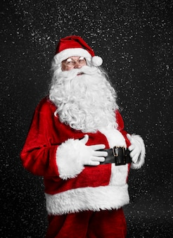 Fröhlicher weihnachtsmann, der seinen bauch zwischen fallendem schnee berührt