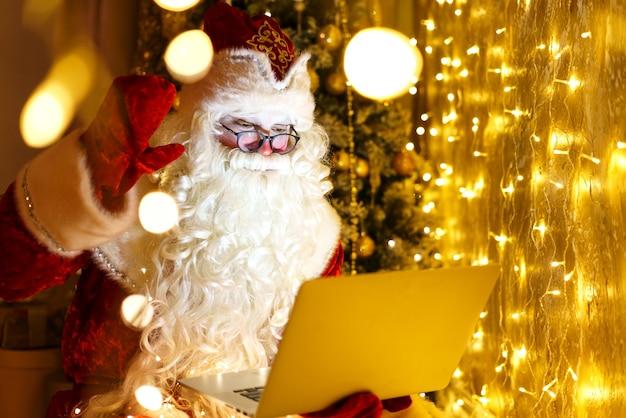Fröhlicher weihnachtsmann im anzug sitzt auf einem sessel mit laptop am heiligabend im online-e-commerce-shop...