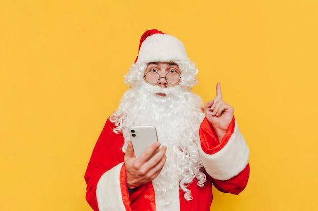 Fröhlicher weihnachtsmann mit smartphone auf gelbem grund