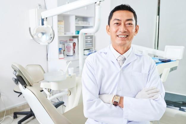 Fröhlicher zahnarzt mit gekreuzten arnen