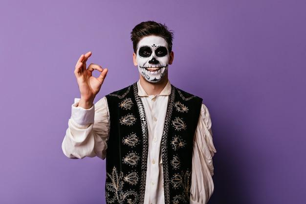 Fröhlicher zombietyp, der auf lila wand lächelt. glücklicher junger mann mit gruseligem make-up, das in halloween mit okayem zeichen aufwirft.