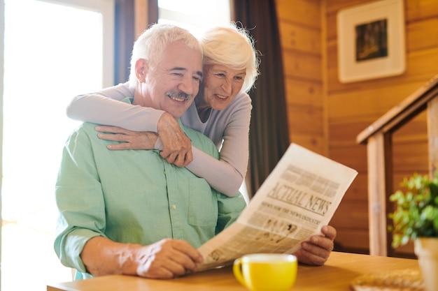 Fröhliches älteres ehepaar in freizeitkleidung, das morgens in seinem landhaus die neuesten nachrichten durchschaut
