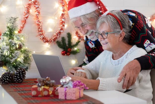 Fröhliches älteres paar, das sich in weihnachtssüßer und weihnachtsmütze umarmt, während es einen laptop verwendet