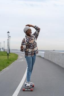 Fröhliches afrikanisches mädchen auf longboard fröhlicher weiblicher skate genießt frische luft und einen extrem aktiven lebensstil