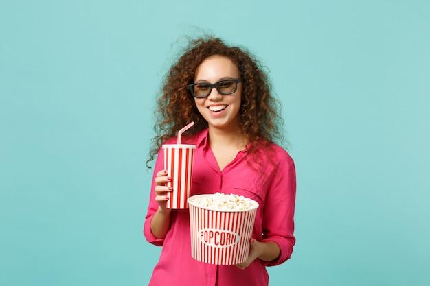 Fröhliches afrikanisches mädchen in 3d-imax-brille, das filmfilm sieht, hält popcorn-tasse soda einzeln auf blauem türkisfarbenem hintergrund im studio. menschen emotionen im kino, lifestyle-konzept. kopieren sie platz.