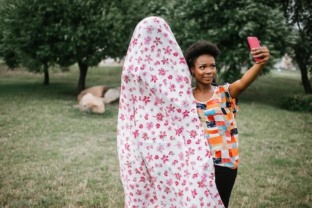 Fröhliches afroamerikanermädchen, das mit einer person im geisterkostüm im freien steht und selfie nimmt. halloween-party-konzept.