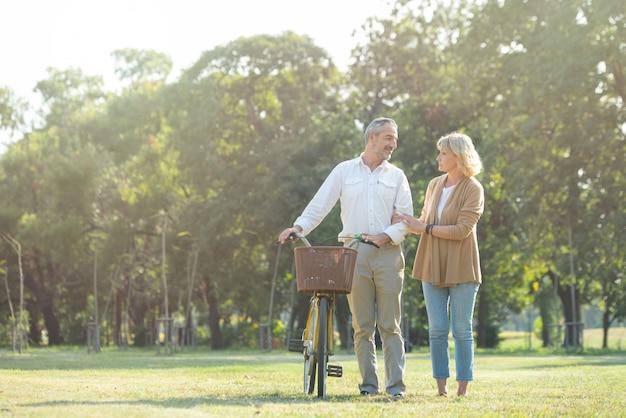 Fröhliches aktives älteres paar mit fahrrad, das zusammen durch park geht. perfekte aktivitäten für ältere menschen im ruhestand.