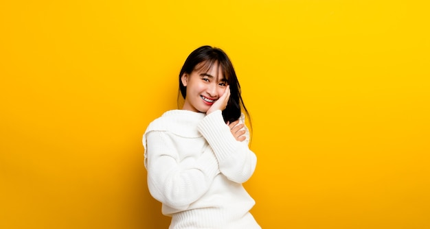 Fröhliches alltagsbild eines glücklichen mädchens, das auf gelbem hintergrund steht und in die kamera schaut und glücklich lächelt