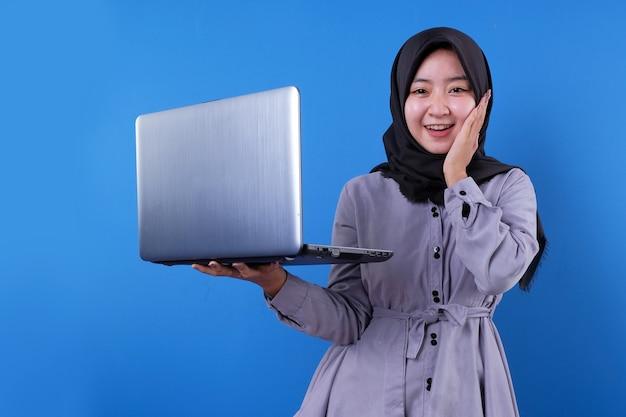 Fröhliches asiatisches frauenlächeln bringen einen laptop und sagen etwas