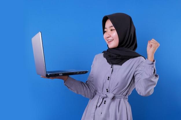 Fröhliches asiatisches frauenlächeln bringen und suchen einen laptop