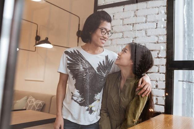 Fröhliches asiatisches junges liebespaar im café.
