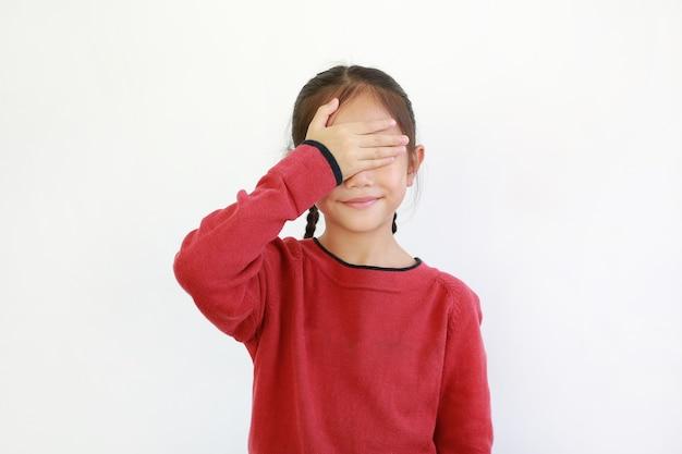 Fröhliches asiatisches kind, das versteckte augen durch eine hand schloss