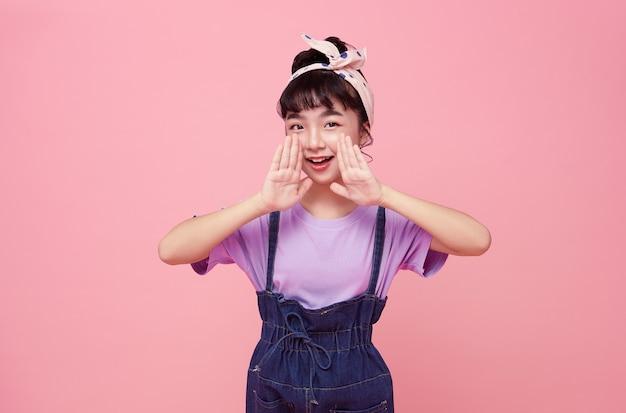Fröhliches asiatisches kind schreit geschichte oder macht eine ankündigung isoliert auf rosa wand.