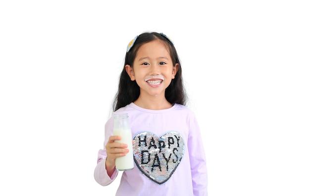 Fröhliches asiatisches kleines kindermädchen, das milch von der glasflasche trennt, lokalisiert auf weißem hintergrund.