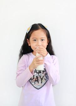 Fröhliches asiatisches kleines mädchen, das milch aus der glasflasche trinkt, die auf weißem hintergrund lokalisiert wird.