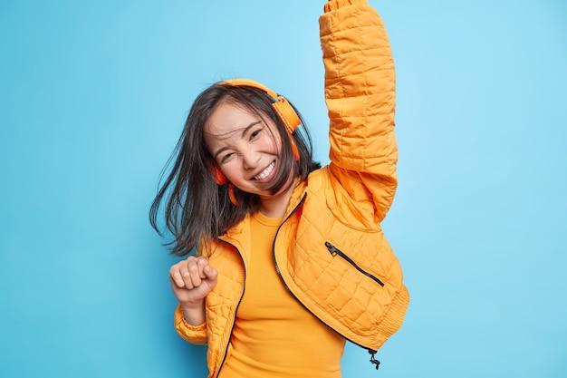 Fröhliches asiatisches mädchen hat lustige dunkle haare, die in der luft schweben, während das springen die arme erhoben hält, drahtlose kopfhörer trägt, musik hört, fühlt sich energisch isoliert über blauer wand menschen leben das glück