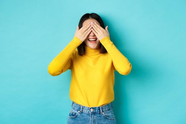 Fröhliches asiatisches mädchen in gelbem pullover, das auf überraschung wartet, verstecken spielen und lächeln, geschenk mit geschlossenen augen erwartend, auf blauem hintergrund stehend