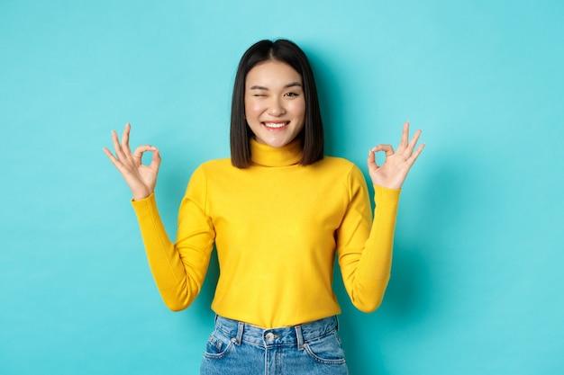 Fröhliches asiatisches weibliches modell, das okaygesten zeigt, lächelnd und beeindruckt aussieht, produkt loben, auf blauem hintergrund stehend.
