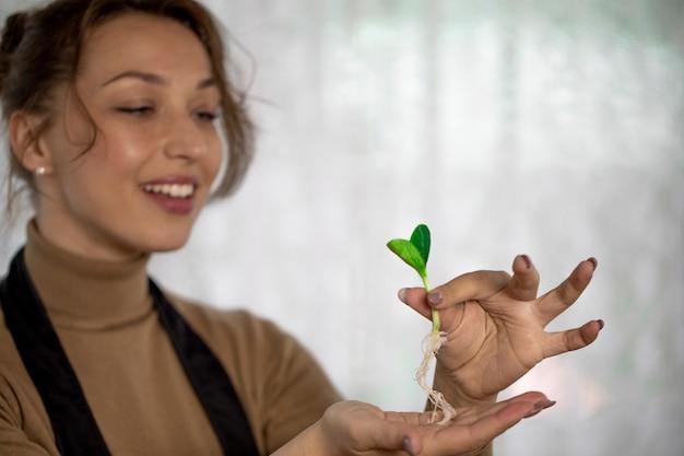 Fröhliches attraktives mädchen mit dem lächeln, das blumenspross hält, bevor man drinnen pflanzt