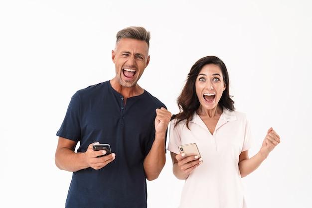 Fröhliches attraktives paar in lässigem outfit, das isoliert über weißer wand steht, mit handy telefoniert und erfolg feiert