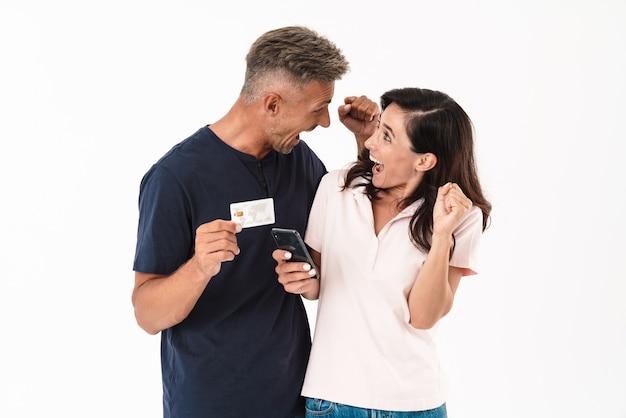 Fröhliches attraktives paar in lässigem outfit, das isoliert über weißer wand steht, online mit handy und kreditkarte einkaufen